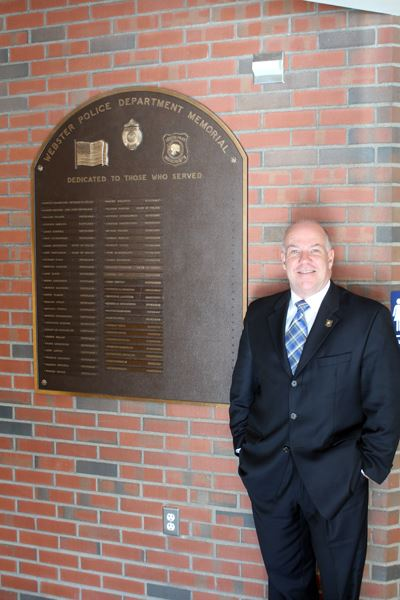 Image of Chief Timothy Bent standing beside wall memorial
